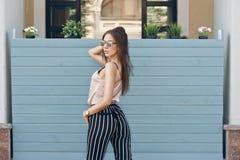 Mooie vrouw, die donkere glazen dragen, tegen de achtergrond van een boommuur Het model draagt modieuze beige kleren, Stock Afbeeldingen