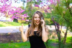 Mooie vrouw die door smartphone spreken en duimen in de lentepark tonen Royalty-vrije Stock Fotografie