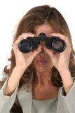 Mooie Vrouw die door Verrekijkers 3 kijkt Stock Foto's