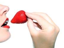 Mooie vrouw die een aardbei eet Royalty-vrije Stock Afbeeldingen