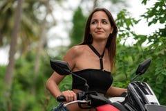 Mooie vrouw die een autoped drijven en zij onderzoekt de afstand Close-up royalty-vrije stock afbeeldingen