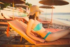 Mooie vrouw die in een bikini op een strand bij tropische reistoevlucht zonnebaden, die de zomer van vakantie genieten Jonge vrou Stock Afbeeldingen