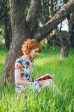 Mooie vrouw die een boek in de de lentetuin lezen stock afbeelding