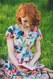 Mooie vrouw die een boek in de de lentetuin lezen royalty-vrije stock foto