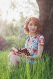 Mooie vrouw die een boek in de de lentetuin lezen royalty-vrije stock foto's