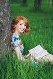 Mooie vrouw die een boek in de de lentetuin lezen stock foto's