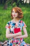 Mooie vrouw die een boek in de de lentetuin lezen royalty-vrije stock fotografie