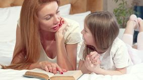 Mooie vrouw die een boek met haar leuke kleine dochter lezen, die op bed thuis liggen stock videobeelden