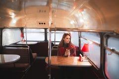 Mooie vrouw die in een deken wordt verpakt, die in een koffiewinkel zitten met een origineel retro binnenland stock afbeelding