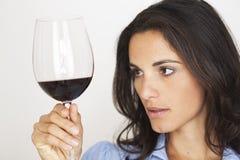 Mooie vrouw die een glas rode wijn controleert stock afbeelding