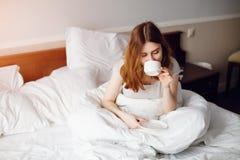 Mooie vrouw die een koffiezitting op haar bedhuis drinken royalty-vrije stock afbeeldingen