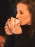 Mooie vrouw die een kop van hete drank drinken dichtbij de haard stock foto's
