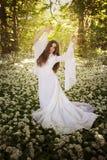 Mooie vrouw die een lange witte kleding dragen die in een bos dansen Stock Afbeeldingen