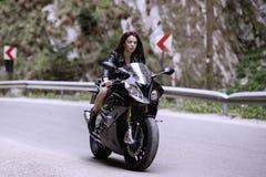 Mooie vrouw die een motorfiets drijven stock foto