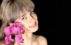 Mooie vrouw die een orchidee houdt dichtbij het gezicht Stock Foto