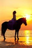 Mooie vrouw die een paard berijden bij zonsondergang op het strand Jonge gir Royalty-vrije Stock Afbeeldingen