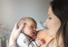 Mooie vrouw die een pasgeboren baby in haar wapens houden stock foto