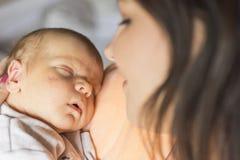 Mooie vrouw die een pasgeboren baby in haar wapens houden stock fotografie
