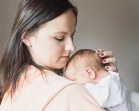Mooie vrouw die een pasgeboren baby in haar wapens houden stock afbeelding