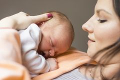 Mooie vrouw die een pasgeboren baby in haar wapens houden royalty-vrije stock afbeeldingen