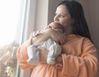 Mooie vrouw die een pasgeboren baby in haar wapens houden royalty-vrije stock foto's