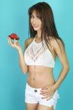 Mooie vrouw die een scherpe aardbei eten Royalty-vrije Stock Foto's