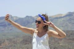 Mooie vrouw die een selfie bovenop een berg, met mooie meningen van de omgeving van teide achter haar, nemen met royalty-vrije stock afbeelding
