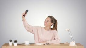 Mooie vrouw die een selfie met haar zitting van de celtelefoon nemen bij het bureau op gradiëntachtergrond stock footage