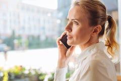 Mooie vrouw die een telefoongesprek in koffie maken royalty-vrije stock foto's