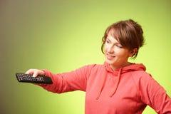 Mooie vrouw die een ver controlemechanisme met behulp van Royalty-vrije Stock Afbeelding