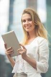 Mooie vrouw die elektronisch lusje in de straat gebruiken royalty-vrije stock foto