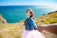 Mooie vrouw die en de mens glimlachen houden met de hand en naar het meer in de bergen bij het gloeien zonsopgang gaan royalty-vrije stock foto's