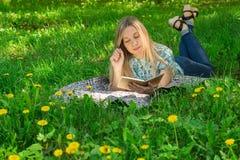 Mooie vrouw die en in haar agenda op het gras met bloemen liggen schrijven Front View Stock Afbeelding