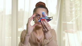 Mooie vrouw die en op een paar moderne glazen schoonmaken zetten stock video