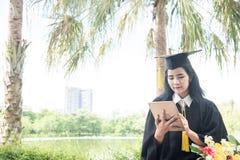 Mooie vrouw die gebruikend tabletpc een diploma behalen De gediplomeerde Aziatische studente die graduatiehoed en toga, achtergro stock afbeeldingen