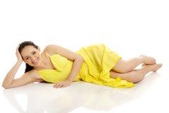 Mooie vrouw die in gele kleding liggen Stock Fotografie