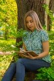 Mooie vrouw die in haar agenda in het park schrijft Royalty-vrije Stock Foto