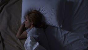 Mooie vrouw die in haar bed draaien die ongemak, slechte kwaliteit voelen van matras stock footage