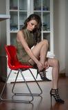 Mooie vrouw die haar benen tonen die of hoge hielen aanzetten opstijgen zwarte schoenen Sensueel aantrekkelijk jong meisje die kl royalty-vrije stock fotografie