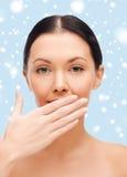 Mooie vrouw die haar mond behandelen Stock Fotografie