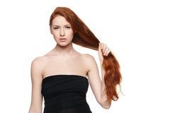 Mooie vrouw die haar rood haar in hand houden stock afbeelding