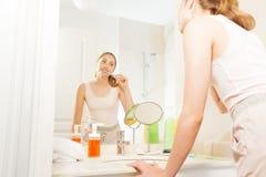Mooie vrouw die haar tanden in de badkamers borstelen stock foto