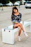 Mooie vrouw die haar telefoon op vrije multifunctionele binnen opgenomen zonnepaneellader laden aan zittingsbank voor burgers Mod royalty-vrije stock foto