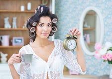 Mooie vrouw die in haarkrulspelden kop van koffie en klok houden Stock Afbeeldingen