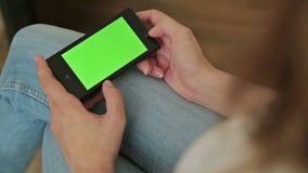 Mooie vrouw die in hand slimme telefoon met groene het schermvertoning houden stock video