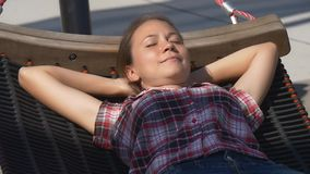 Mooie vrouw die in hangmat in stadspark dutten stock video