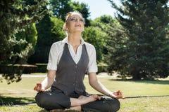 Mooie vrouw die in het park mediteren Stock Fotografie