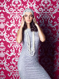 Mooie vrouw die het zilveren kleding en hoeden stellen op ornamentallachtergrond dragen Stock Foto's