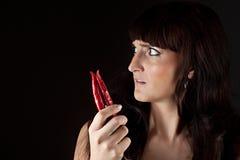 Mooie vrouw die hete kruidige Spaanse peperpeper kijken Stock Afbeeldingen