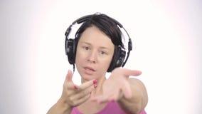 Mooie vrouw die in hoofdtelefoons dansen terwijl het luisteren aan een muziek op een lichte achtergrond stock footage